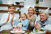 Happy family members clapping their hands while little girl going to blow candles on birthday cake poster