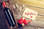 Valentines day greeting card. Red wine and gift box on wooden table. Top view with copy space poster