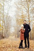 Couple In Love Walking In The Autumn Park, Cool Fall Weather. A Man And A Woman Embrace And Kiss, Lo poster