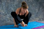 picture of fireflies  - A brown haired caucasian woman is doing advanced asana yoga exercise Tittibhasana Pose or Firefly posture on yoga mat in studio with mottled background - JPG