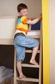 ¿Niño sonriente subiendo la escalera de la litera.?