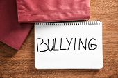 Notebook with word Bullying on wooden background poster