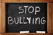 Chalkboard with text Stop bullying, closeup poster
