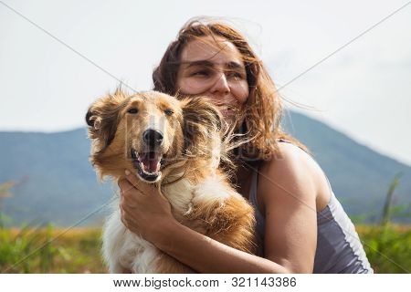 poster of Woman Hugging Scotch Collie Dog In Meadow. Woman Hugging Scotch Collie Dog In Nature. Close Up Of Sc