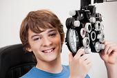 Smiling boy holding phoropter while undergoing an eye examination.