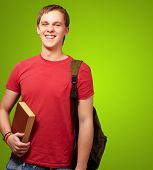portrait of a young student holding a book and carrying a backpack over a green background