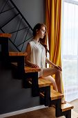 Beautiful Redhead Woman Posing On The Staircase In Loft Apartment. poster