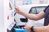 Man Charging Electric Vehicle Paying For Energy With Credit Card At Charging Station poster