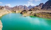 Scenic view of Hatta Lake and Hajar Mountains in the Emirate of Dubai, UAE poster