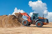 Backhoe Loader Or Bulldozer - Excavator With Clipping Path On A Background With Blue Sky And Clouds. poster