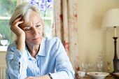 Senior Woman Suffering With Depression With Head In Hands At Home poster