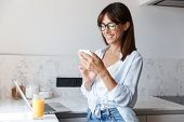Image of a young beautiful cheerful happy business woman indoors at home at the kitchen using laptop poster