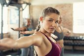 Closeup face of determined woman doing aerobic exercises at gym standing with arms outstretched. Det poster