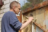 Man painting gate .Ukraine