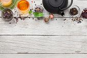 Different herbal and fruit dry teas and cups on wooden table. Top view flat lay with copy space poster