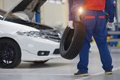 Handsome Young Auto Mechanic In Uniform Is Examining A Tire While Working In Auto Service Mechanic H poster