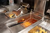 Deep fryer with boiling oil in commercial kitchen, fast food restaurant poster