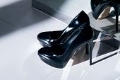 Black Patent Leather High-heeled Shoes Standing On The Floor Near The Mirror. High Heel Shoes. A Pai poster
