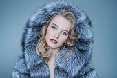 A close up portrait of a beautiful woman wearing a fur coat with hood. Beauty, winter fashion, style poster