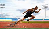 Man sprinter leaving starting blocks on the athletic track poster