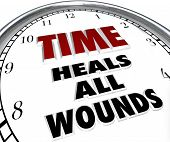 stock photo of pass-time  - The saying Time Heals All Wounds on the face of a clock illustrating the forgiveness and resolved disputes that only the passing of time can bring about - JPG