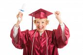Senior woman dressed in her graduation cap and gown, raises her arms in excitement over getting her