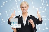 Multi-tasking estate agent holding keys and model home while giving thumbs up against a blueprint background