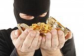 stock photo of plunder  - Masked man is holding stolen gold - JPG