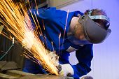 stock photo of manufacturing  - A construction worker using an angle grinder producing a lot of sparks - JPG