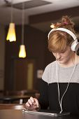 image of nose ring  - A young woman listens to music on her headphones with an electronic tablet - JPG