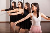 stock photo of ballet barre  - Cute female ballet dancers training in a ballet barre in a dance academy - JPG