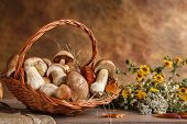 stock photo of eatables  - studio photography of wicker basket with eatable mushrooms - JPG