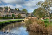 stock photo of slaughter  - Row of Cotswold cottages on the River Eye - JPG