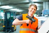 Logistics - Warehouseman with protective vest and scanner, scans bar-code of package, he standing at
