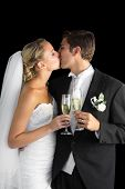 Lovely married couple kissing each other holding champagne glasses