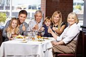 Happy family congratulate in restaurant holding their thumbs up