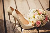 stock photo of bouquet  - Close up of wedding bouquet and bride shoes - JPG