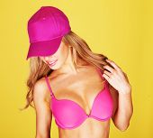 Trendy young woman with long blond hair dancing in a pink bikini and matching peaked cap with a smile of pleasure on her face against a yellow background