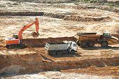loader excavator machine loading dumper truck at sand quarry