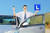 Happy young man posing near his car, holding a L sign and car key after having his driver's licence