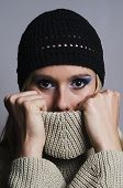 blonde woman covering her face with turtleneck vertical
