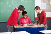 Young African American female teacher teaching students at desk in classroom