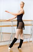 picture of ballet barre  - Wearing leotard and warmers female ballet dancer dances near barre and mirrors in dancing hall - JPG