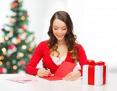christmas, x-mas, valentine's day, celebration concept - smiling woman in red clothes with gift box