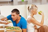 healthy and unhealthy nutrition concept - bright picture of couple eating different food