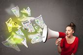 picture of yell  - Cute girl yelling into loudspeaker and newspapers fly out - JPG