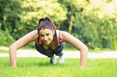 Smiling fit woman doing plank position looking at camera on the grass