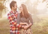 stock photo of jeans skirt  - Young couple in love walking in the autumn park holding hands looking in the sunset - JPG