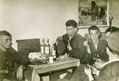 LODZ, POLAND, CIRCA 1970's: Vintage photo of  group of servicemen drinking alcohol and smoking toget
