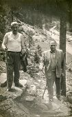 LODZ, POLAND, CIRCA 1960's: Vintage photo of two mature men walking with wooden sticks in mountains